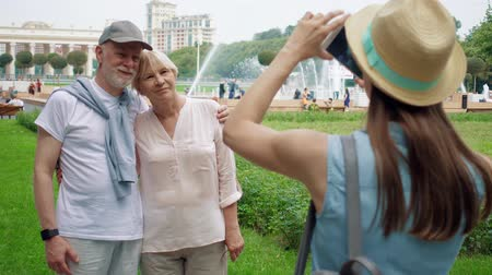 Seniors and their teenage daughter having great time in Gorky Park. Happy family enjoying vacation together. Daughter taking photo of her senior parents on vacation trip in Moscow, Russia