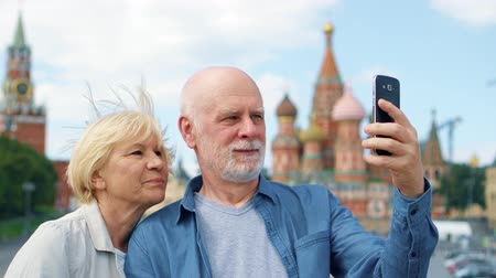 Snior couple stand on Basils Descent do selfie on mobile phone. Traveling pensioners make photo in Moscow, Russia. Red Square, St. Basils Cathedral and Kremlin clock on background. Hand-held camera Wideo