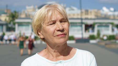 Portrait of blond smiling woman standing outdoors looking at camera. Female pensioner traveling in Moscow, Russia. People walking around. Hand-held camera Wideo