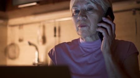 Senior woman working on laptop from home office in evening. Smiling retired female freelancer using mobile phone to discuss project with colleague at night. Overworked businesswoman in kitchen at home Wideo