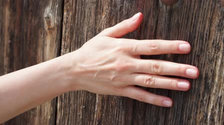 Woman sliding hand against old wooden door in slow motion. Female hand touching hard rough surface of wood on sunny summer day
