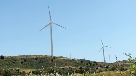 Green hill with windmills in Larnaca, Cyprus. Wind power technology - wind turbine against blue sky. Clean and renewable energy resource of alternative energy production Wideo