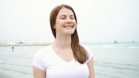 Happy smiling young woman in white t-shirt walking along beach alone. Wind from sea blowing female hair in slow motion. Vacation during off-season on Mediterranean Sea Wideo