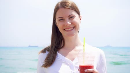 Smiling vegan woman in white shirt holding cup with strawberry smoothie against sea in slow motion. Fit vegetarian female enjoying healthy lifestyle outdoors