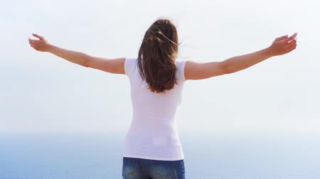Smiling young woman in white t-shirt spining at cliff against breathtaking view of blue sea. Carefree female raising arms up and dancing in slow motion. Happy overjoyed girl whirling around herself Wideo