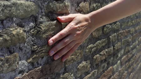 Woman sliding hand against old ancient red brick wall in slow motion. Female hand touching hard rough surface of stone bridge