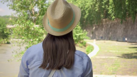 wanderlust : Young woman in hat walking along waterfront in slow motion. Behind view of happy female traveler enjoying vacation outdoors. Concept of new experience and freedom in traveling