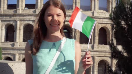 цыган : Young woman standing near famous attraction Colosseum in Rome, Italy. Teenage girl waving Italian flag in slow motion. Happy female tourist enjoying european vacation. Student travel through Europe