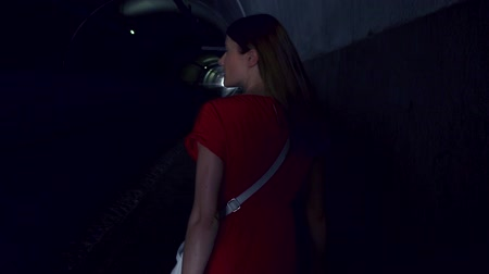 Back view of young woman in red dress walking alone in tunnel at night. Scared female running fast from her pursuer at night. Girl turning around to see who is behind. Concept of crime and violence Wideo