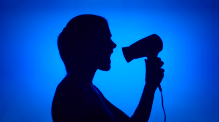 Silhouette of young woman having fun singing into hair dryer. Females face in profile pretending to hear music dancing silly on blue background. Black contour shadow of teenagers half-face singing