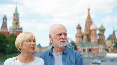 Happy senior couple standing on Basils Descent looking around city. Pensioners traveling in Moscow, Russia. Red Square, St. Basils Cathedral and Kremlin clock tower on background. Hand-held camera