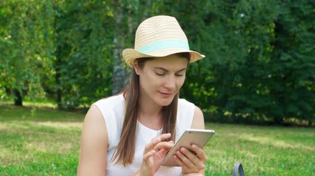Young female student in white shirt sitting on grass on college campus with mobile phone. Tourist in hat chatting with friends on smart phone in public park enjoying summer sunny day Wideo
