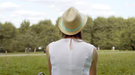 Young lonely female student in white shirt sitting on grass on college campus relaxing. Calm tourist in hat daydreaming in public park enjoying summer day. Concept of loneliness and freedom