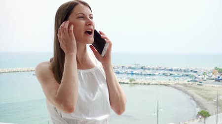 Smiling young woman in white dress using mobile on balcony. Female on vacation enjoying sea view from terrace in morning and talking to friend via cellphone in slow motion