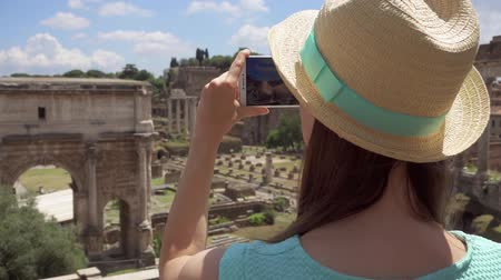 Woman in hat near ancient ruins Forum Romanum taking photo on mobile phone in slow motion. Happy female tourist taking picture of Roman forum in center of Rome, Italy. Student travel through Europe