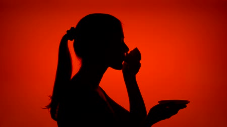 Silhouette of young woman with cup of coffee on red background. Females face in profile drinking coffee from mug. Black contur shadow of teenagers half-face