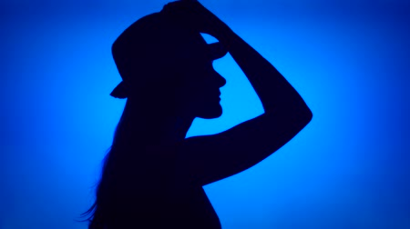 Silhouette of young woman putting on hat on head. Females face in profile with headwear on blue background. Black contour shadow of teenagers half-face Wideo