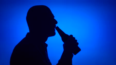 Silhouette of senior man opening can beer bottle on blue background. Males face in profile drinking beer from glass bottle. Black contur shadow of grandfathers half-face