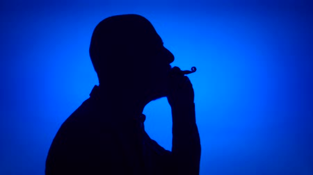Silhouette of senior man using birthday whistle on blue background. Males face in profile celebrating. Black contur shadow of grandfathers half-face. Celebration concept