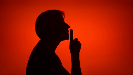 barulhento : Silhouette of senior woman on red background. Females face in profile put finger to lips making silence gesture. Black contur shadow of grandmothers half-face shush. Concept of mystery and secrecy