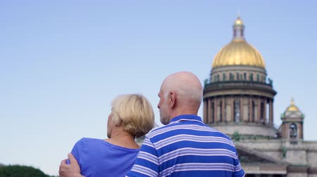 Back view of senior couple standing near Saint Isaacs Cathedral looking around city. Happy loving pensioners traveling in Saint Petersburg, Russia. Hand-held camera