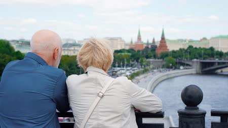 arka görünüm : Back view of happy senior couple standing on observation deck looking around city. Pensioners traveling in Russia viewing attractions. Moscow city landscape and river on background. Hand-held camera