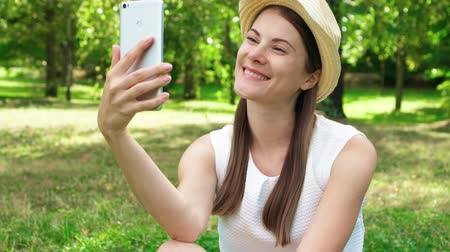 Young female student in white shirt sitting on grass on college campus using mobile phone. Tourist in hat having video chat via online app on cellphone in public park enjoying summer sunny day Wideo