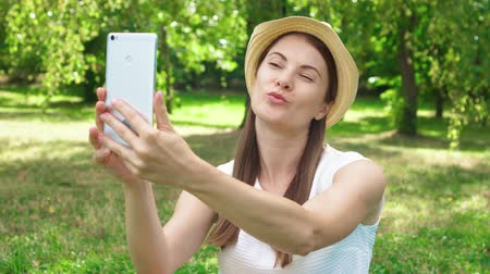 field study : Young female student in white shirt sitting on grass on college campus doing selfie on mobile phone. Tourist in hat make photos on smart phone in public park enjoying summer sunny day