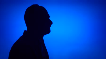 Silhouette of senior man putting on big black wireless headphones on blue background. Males face in profile listening to music. Black contur shadow of grandfathers half-face singing Stok Video