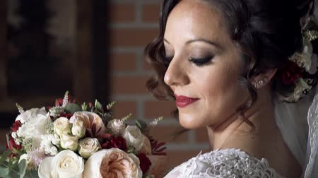 smelling : The bride looks at the wedding bouquet and corrects it. Tenderness. Sniffing a bouquet. Slow motion
