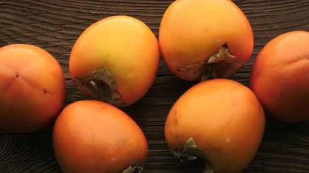 persimmons : Fresh orange persimmons on wooden table. Delicious orange persimmons.