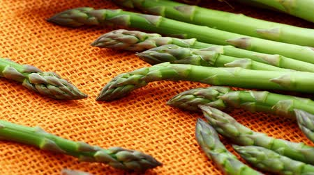 pano de saco : Fresh asparagus officinalis isolated on orange background. Raw garden asparagus stems. Vídeos