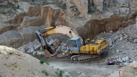 погрузчик : Mining in the granite quarry. Working mining machine - old digger. Mining industry.
