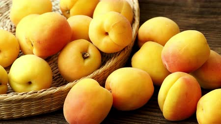 абрикосы : Ripe juicy apricots in a basket on a wooden background