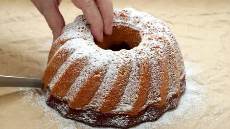 powdered : Slicing the cake. Traditional homemade marble cake. Sliced marble bundt cake on paper. 4k resolution. Stock Footage