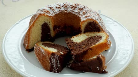 entire : Traditional homemade marble cake. Sliced marble bundt cake on white plate