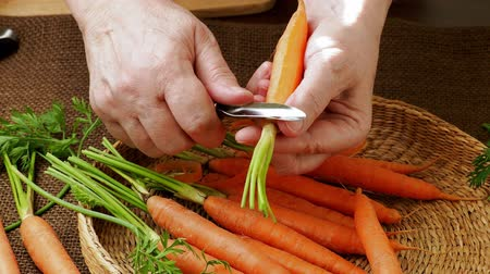 soyulması : Root vegetable. Closeup womans hands peeling carrot. Stok Video