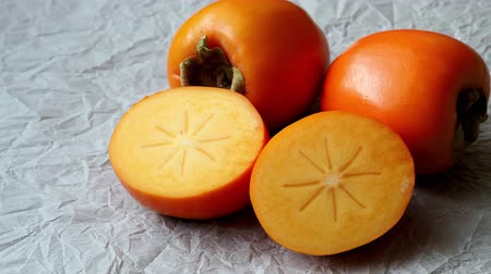 persimmons : Whole and half of fresh ripe persimmons. Japanese persimmon (Diospyros kaki) Stock Footage