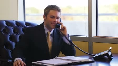 makler : Smiling blond businessman in suit and tie at work talking to a customer to the phone about real estate.