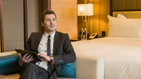 отель : Working in hotel room. Confident young businessman in suit and tie working on digital tablet while sitting on the couch in hotel room Стоковые видеозаписи