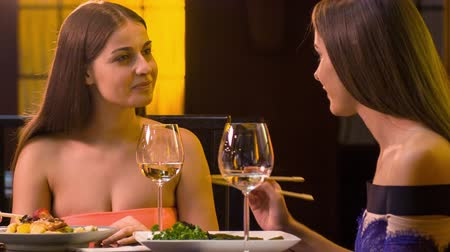 restoran : Chattering between friends. Two smiling young women sitting in stylish Japanese restaurant talking and eating their dishes with chop sticks Stok Video