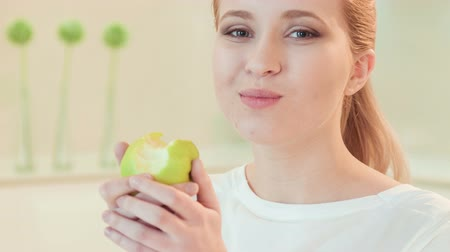 perda de peso : That is delicious. Selective focus on young red-haired smiling woman standing in her kitchen eating fresh ripe apple showing us healthy way of life