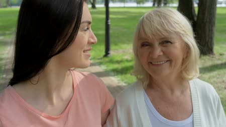 falar : Pleasant woman and her senior mother walking in the park