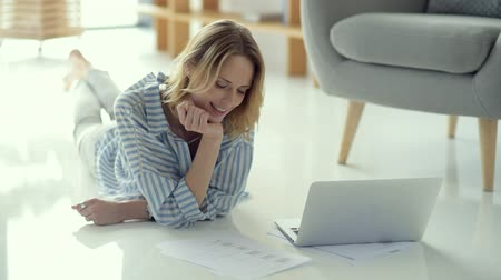 self motivated : Pensive female freelancer working with documents while lying on floor