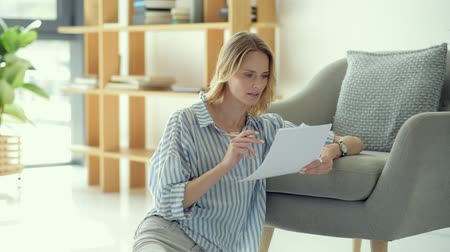 self motivated : Beautiful young lady checking business documents at home Stock Footage