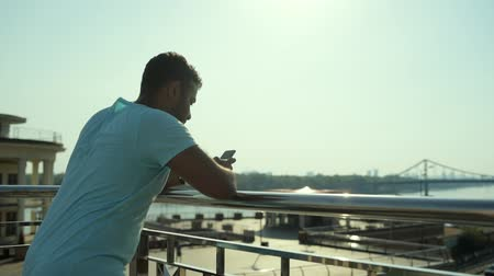 modern manhood : Rear view of handsome man walking and exchanging messages Stock Footage