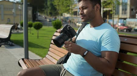 modern manhood : Skilled young Indian man taking photos outdoors