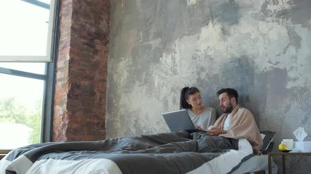 chřipka : Young married couple working on laptop in bed