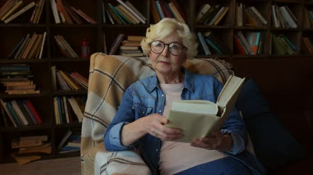 книги : Pleasant time. Delighted nice senior woman reading a book and sitting in the arm chair while enjoying time at home
