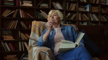 книги : Share your wisdom. Nice elderly woman sitting in her home library and reading a book Стоковые видеозаписи